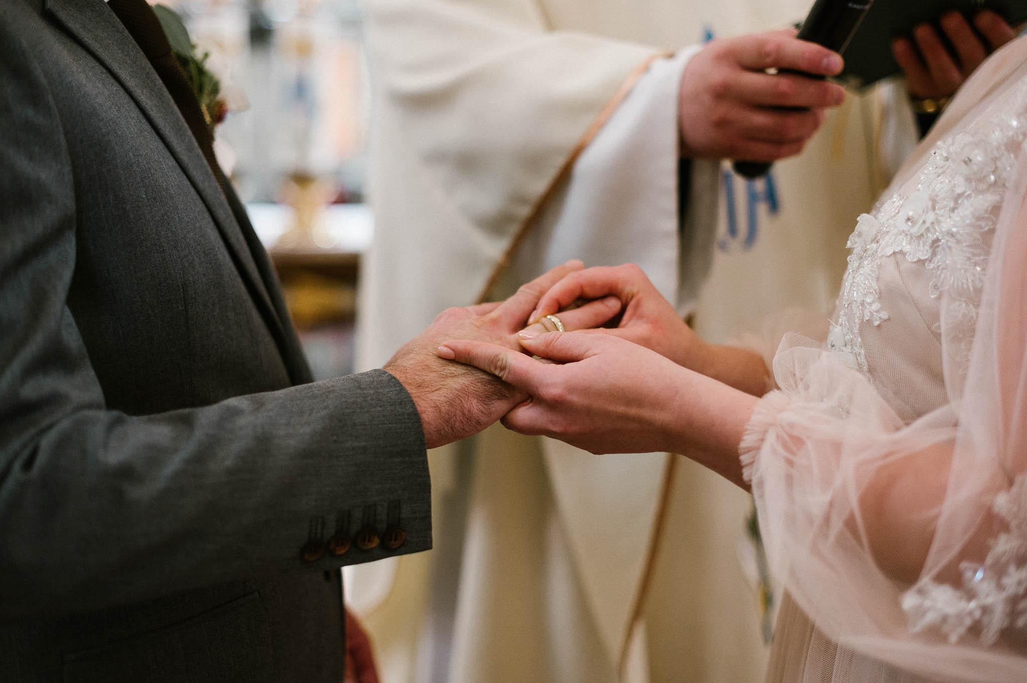 Panna młoda zakłada mężowi obrączkę - ślub w Biskupicach, Siedem Drzew