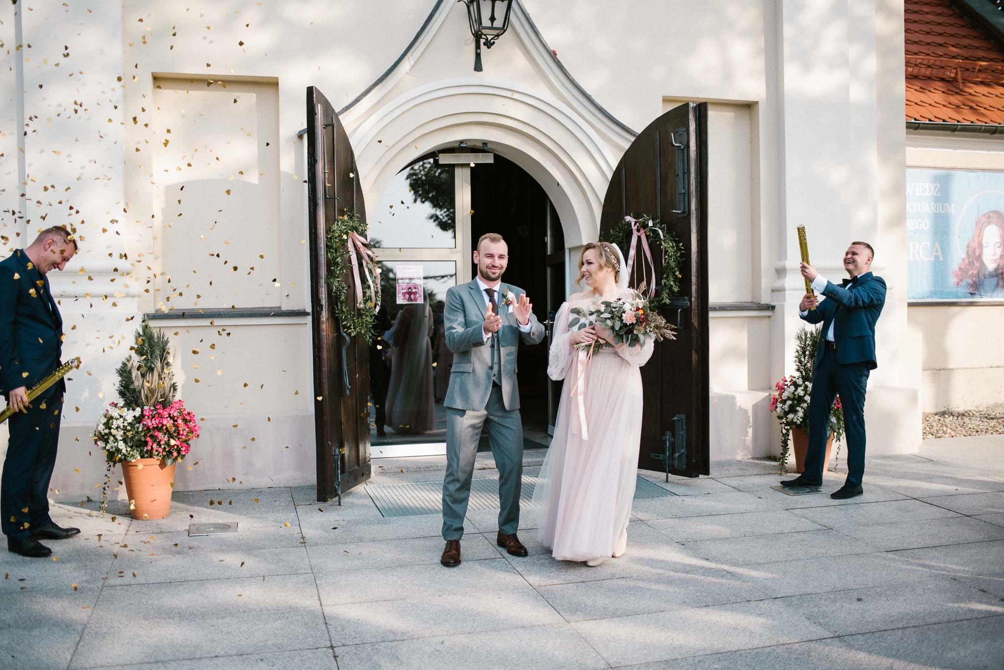Para młoda wychodzi z kościoła w Poznaniu- ślub w Biskupicach, Siedem Drzew