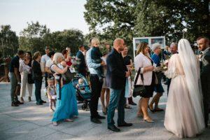 Goście przed kościołem w Poznaniu - ślub w Biskupicach, Siedem Drzew