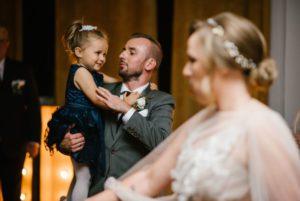 Pan młody trzyma dziewczynkę na rękach - ślub w Biskupicach, Siedem Drzew
