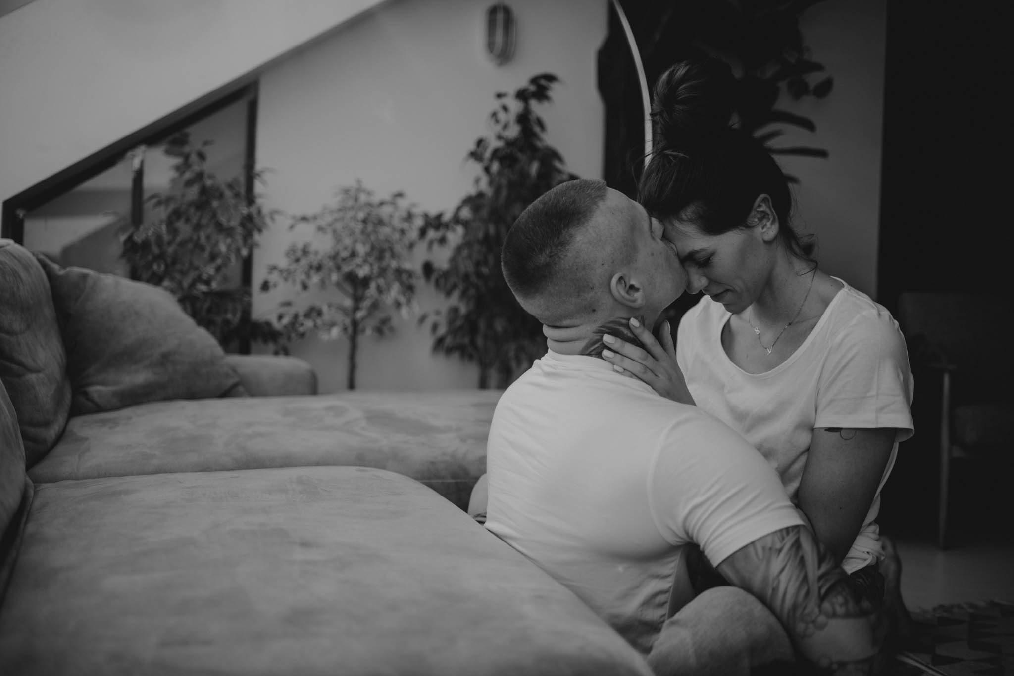 Mężczyzna całuje partnerkę w czoło - sesja miłosna w domu w Poznaniu