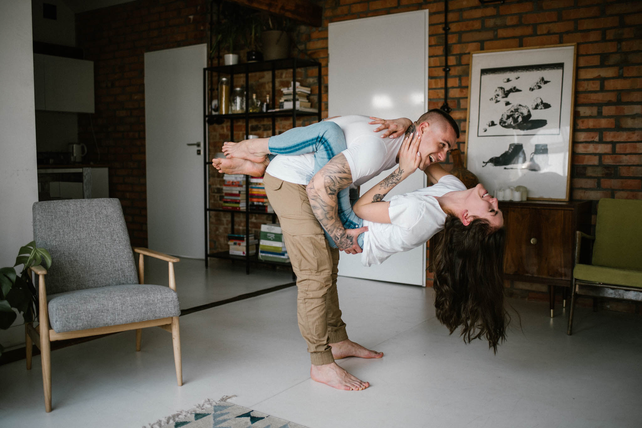 Mężczyzna podnosi kobietę - sesja miłosna w domu w Poznaniu