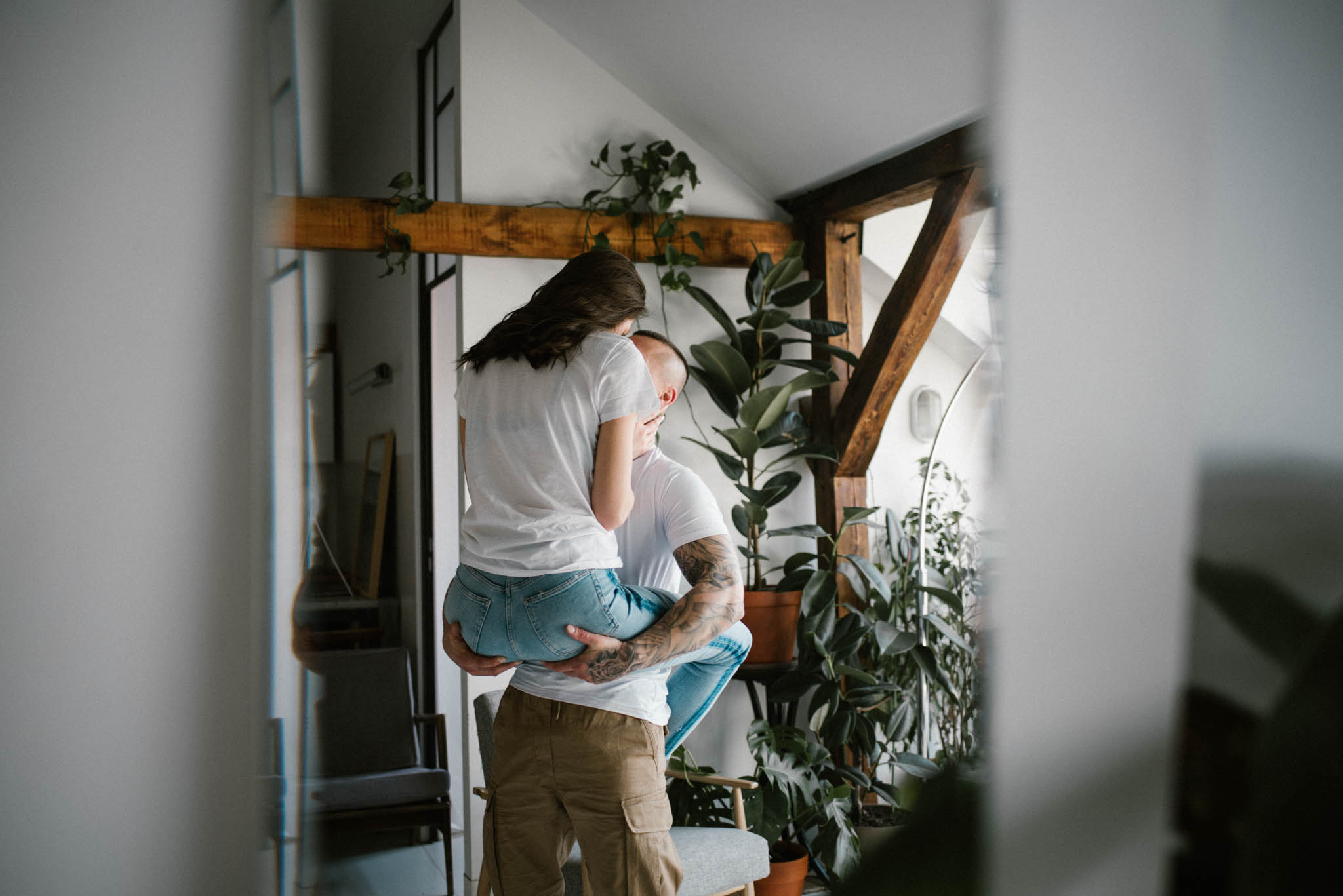 Para całuje się, mężczyzna trzyma kobietę na rękach -sesja miłosna w domu w Poznaniu