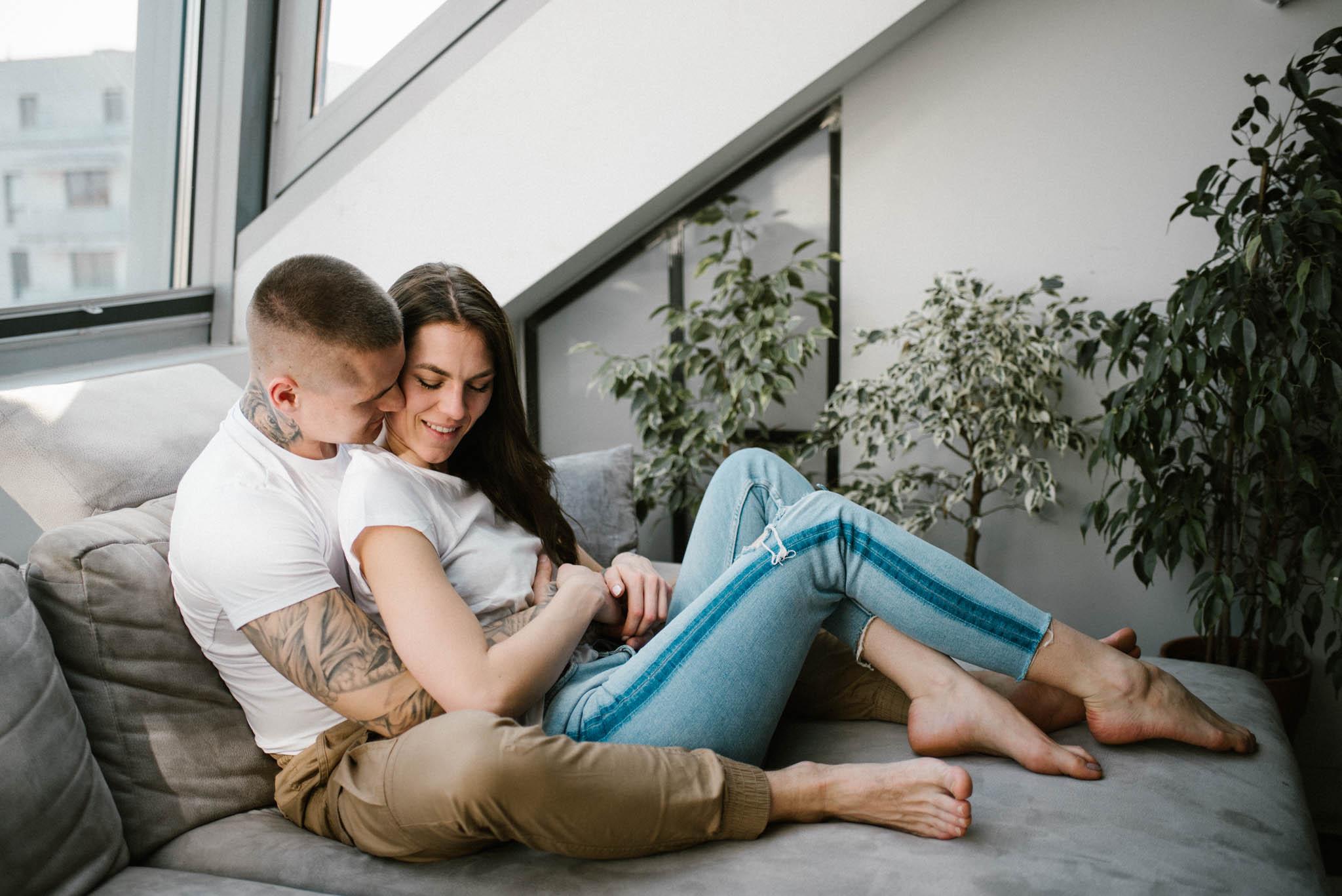 Kobieta i mężczyzna przytulają się na sofie - sesja miłosna lifestyle Poznań Pani Woźna