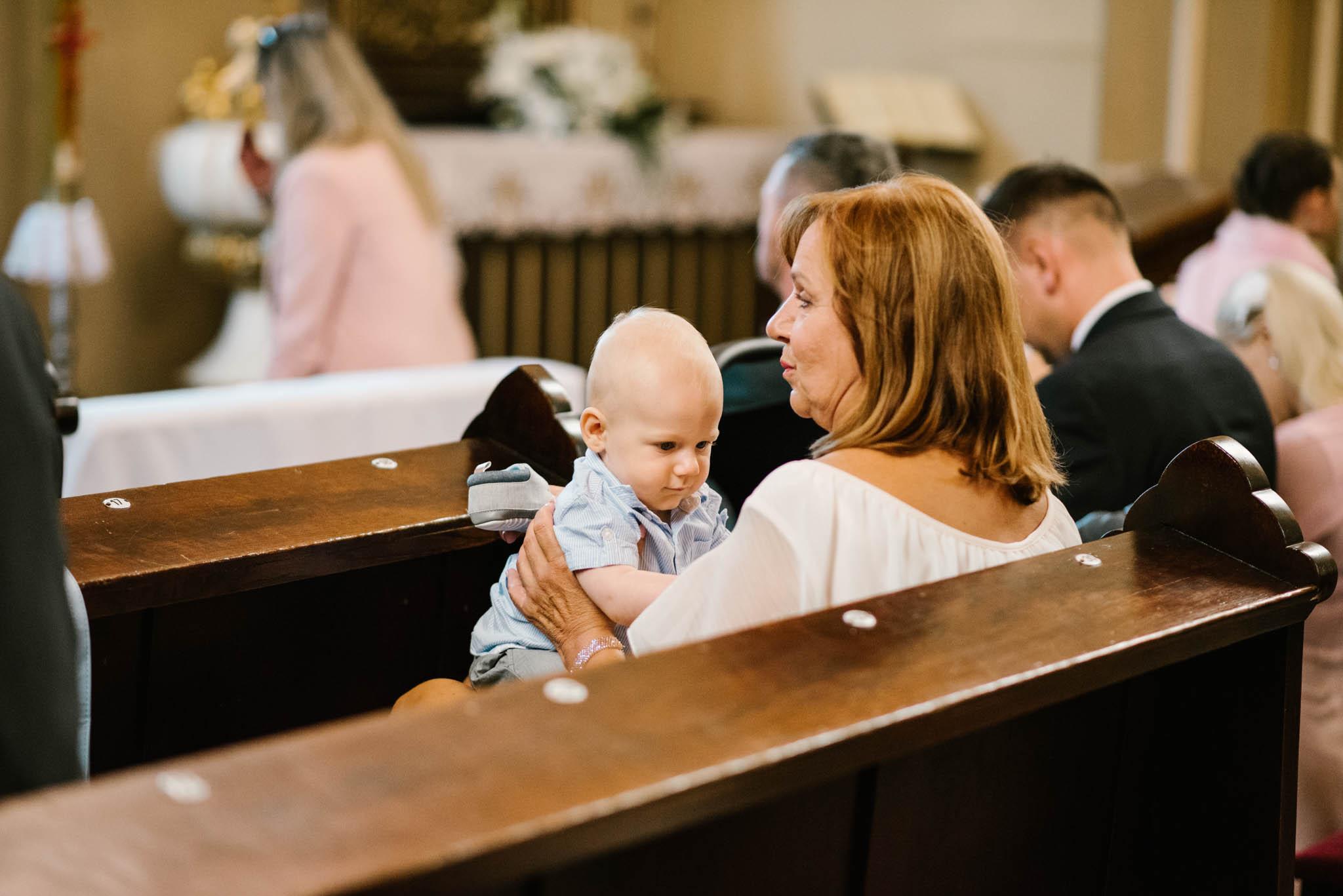 Małe dziecko w kościele na ślubie - sesja ślubna na Wyspie Św. Edwarda Zaniemyśl