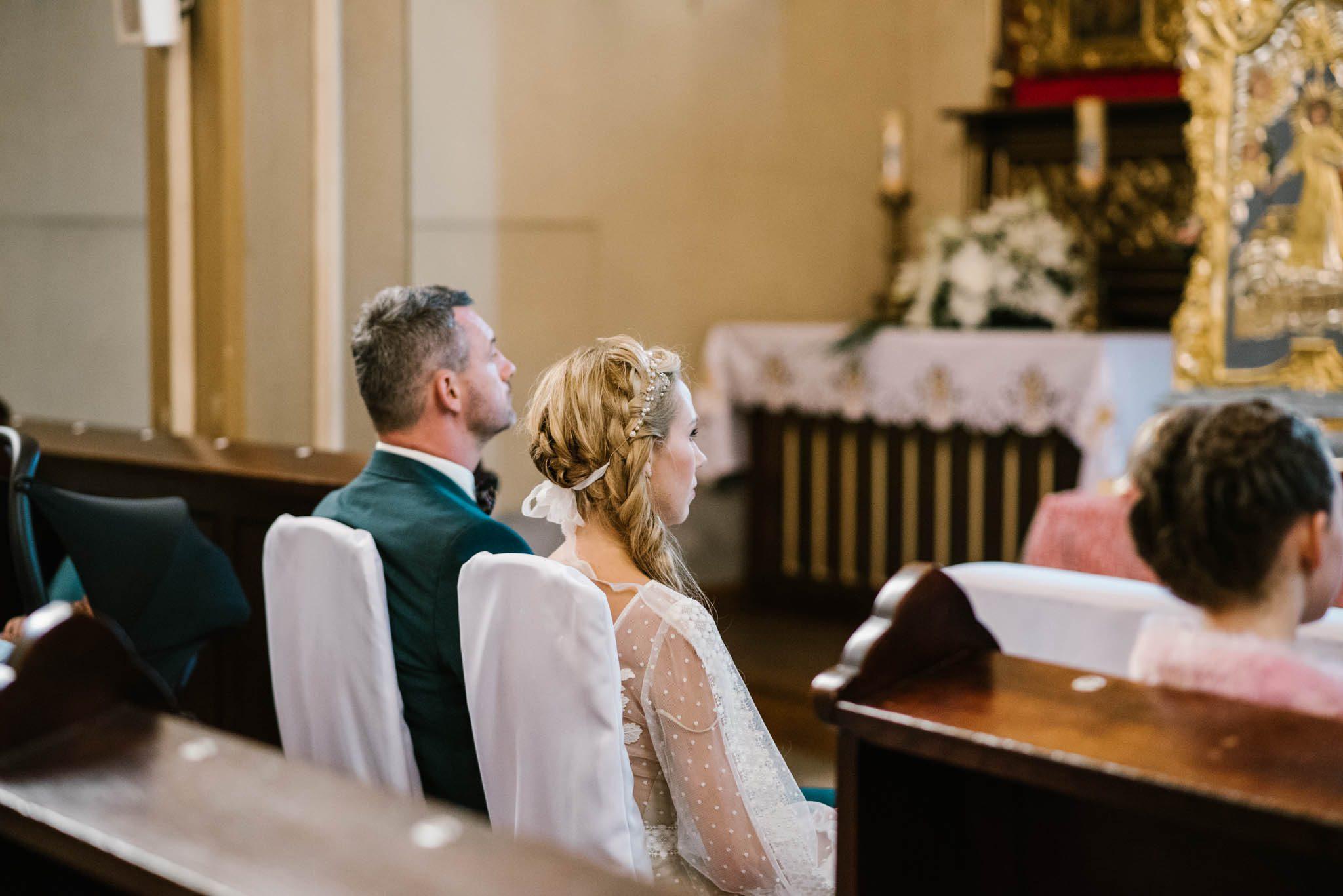 Para młoda siedzi przed ołtarzem w kościele - sesja ślubna na Wyspie Św. Edwarda Zaniemyśl