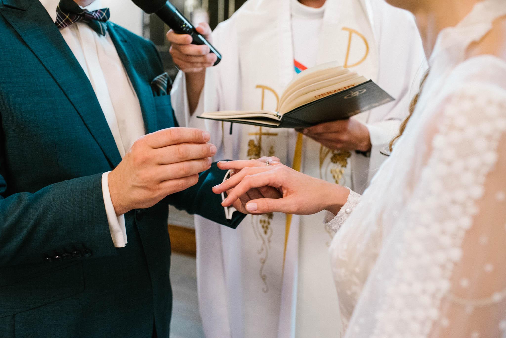 Pan młody zakłada pani młodej obrączkę - sesja ślubna na Wyspie Św. Edwarda Zaniemyśl