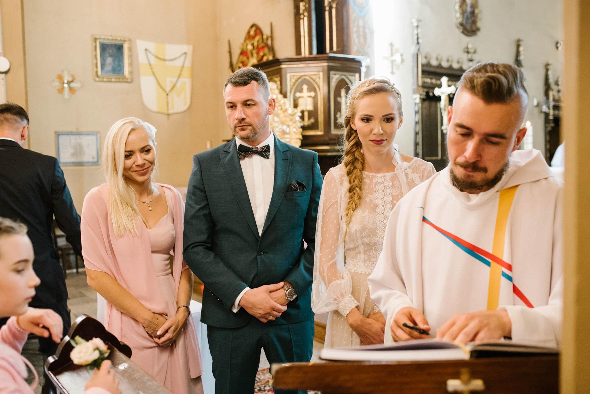 Małżeństwo podpisuje dokumenty w kościele - sesja ślubna na Wyspie Św. Edwarda Zaniemyśl