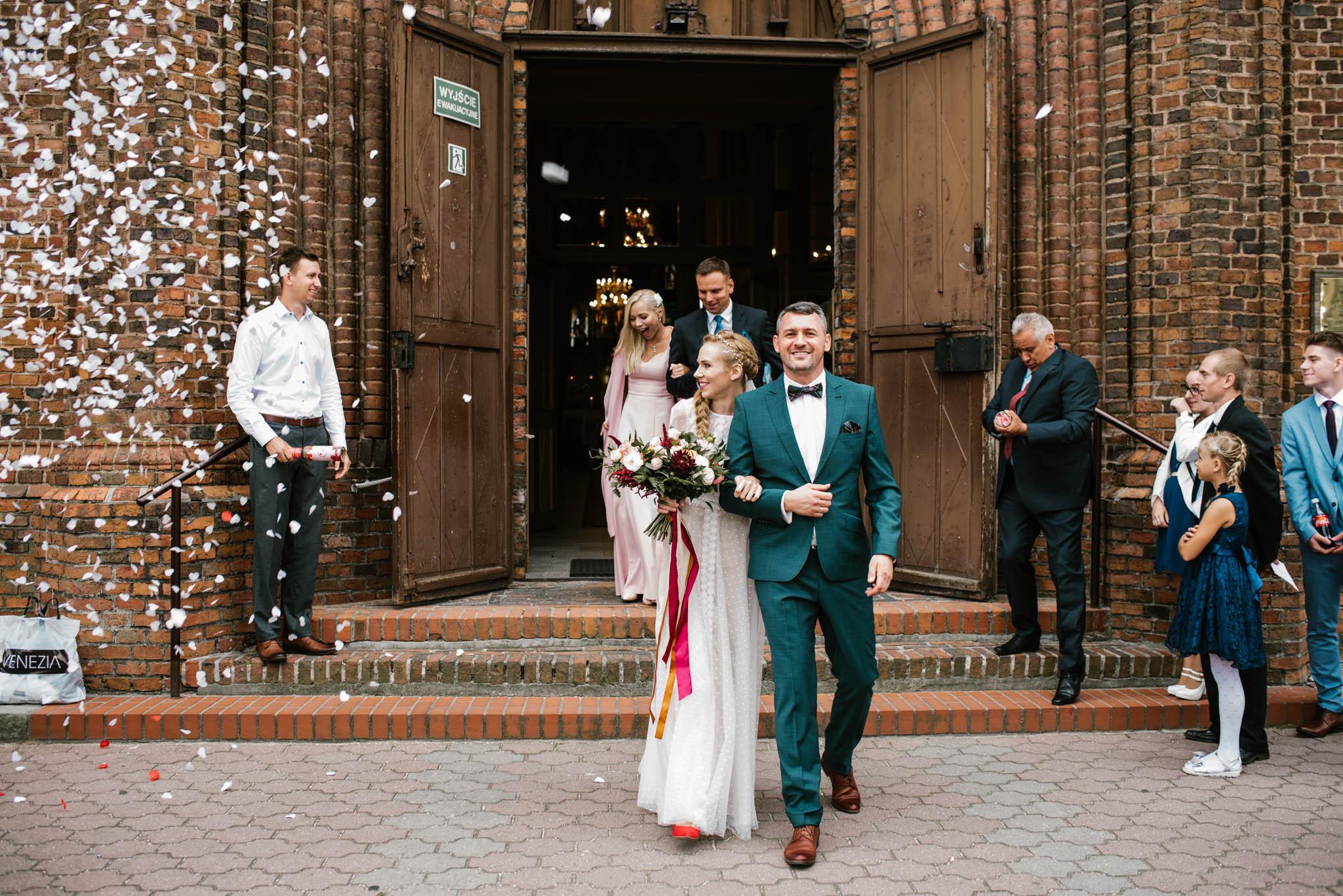 Państwo młodzi wychodzą z kościoła - sesja ślubna na Wyspie Św. Edwarda Zaniemyśl