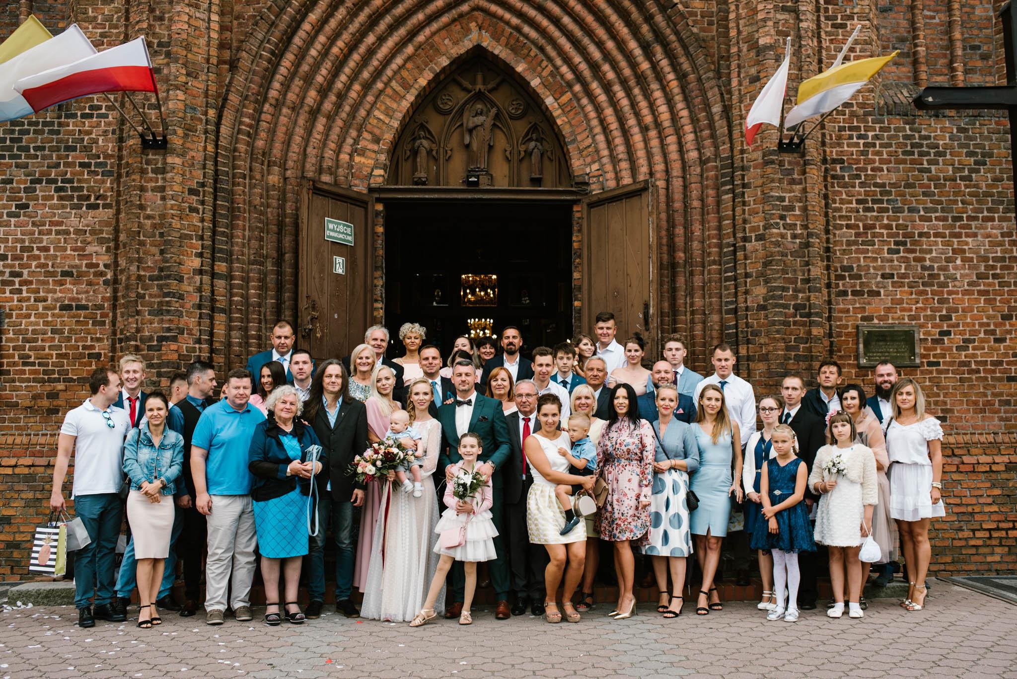Wspólne zdjęcie gości weselnych przed kościołem - sesja ślubna na Wyspie Św. Edwarda Zaniemyśl