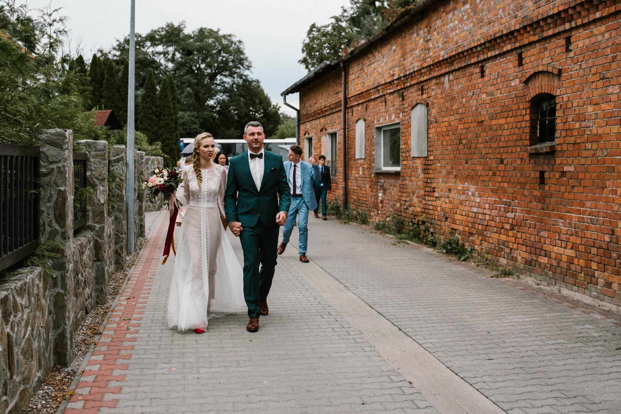 Pan i pani młoda idą chodnikiem - sesja ślubna na Wyspie Św. Edwarda Zaniemyśl