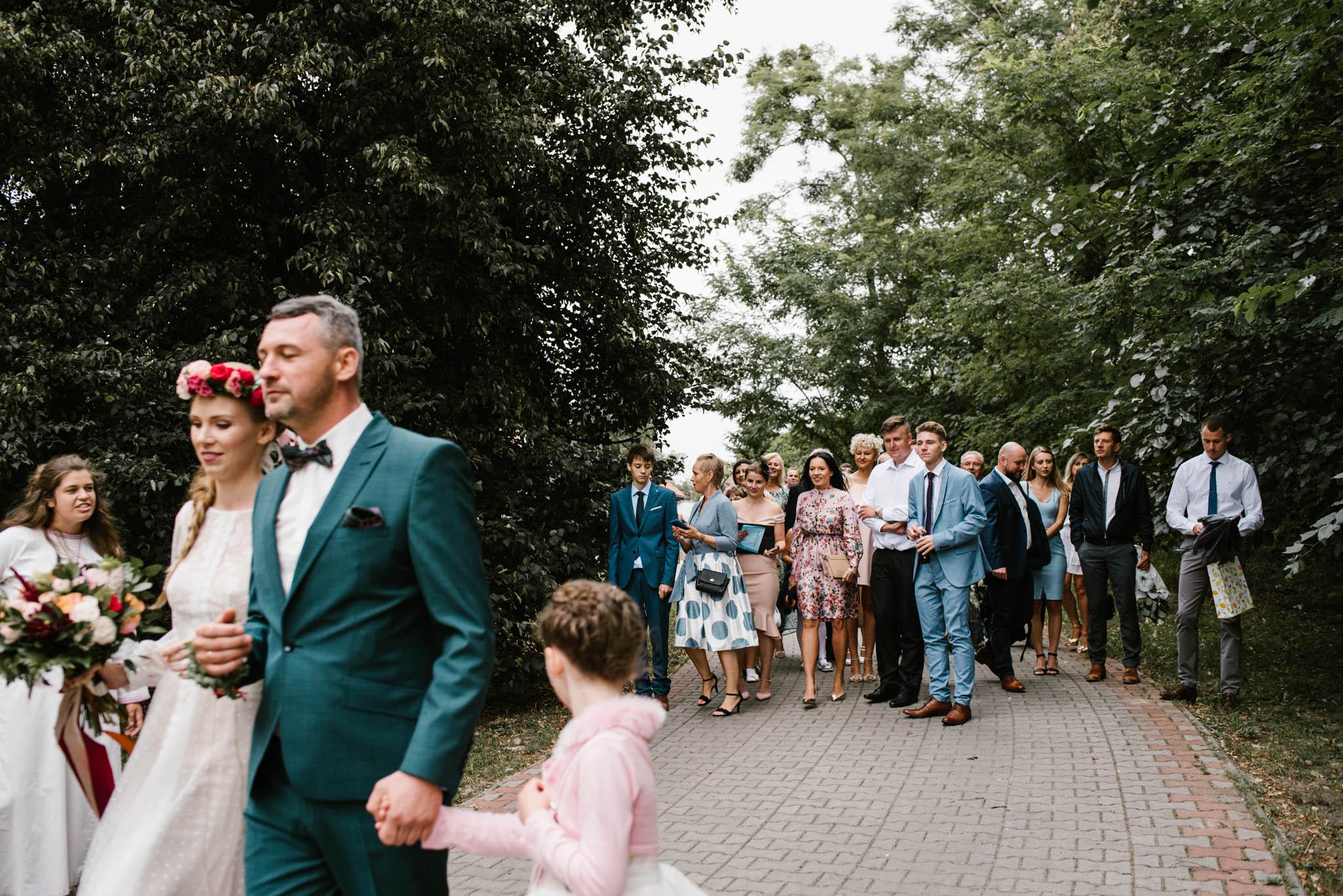 Rodzina i znajomi idą za parą młodą - sesja ślubna na Wyspie Św. Edwarda Zaniemyśl