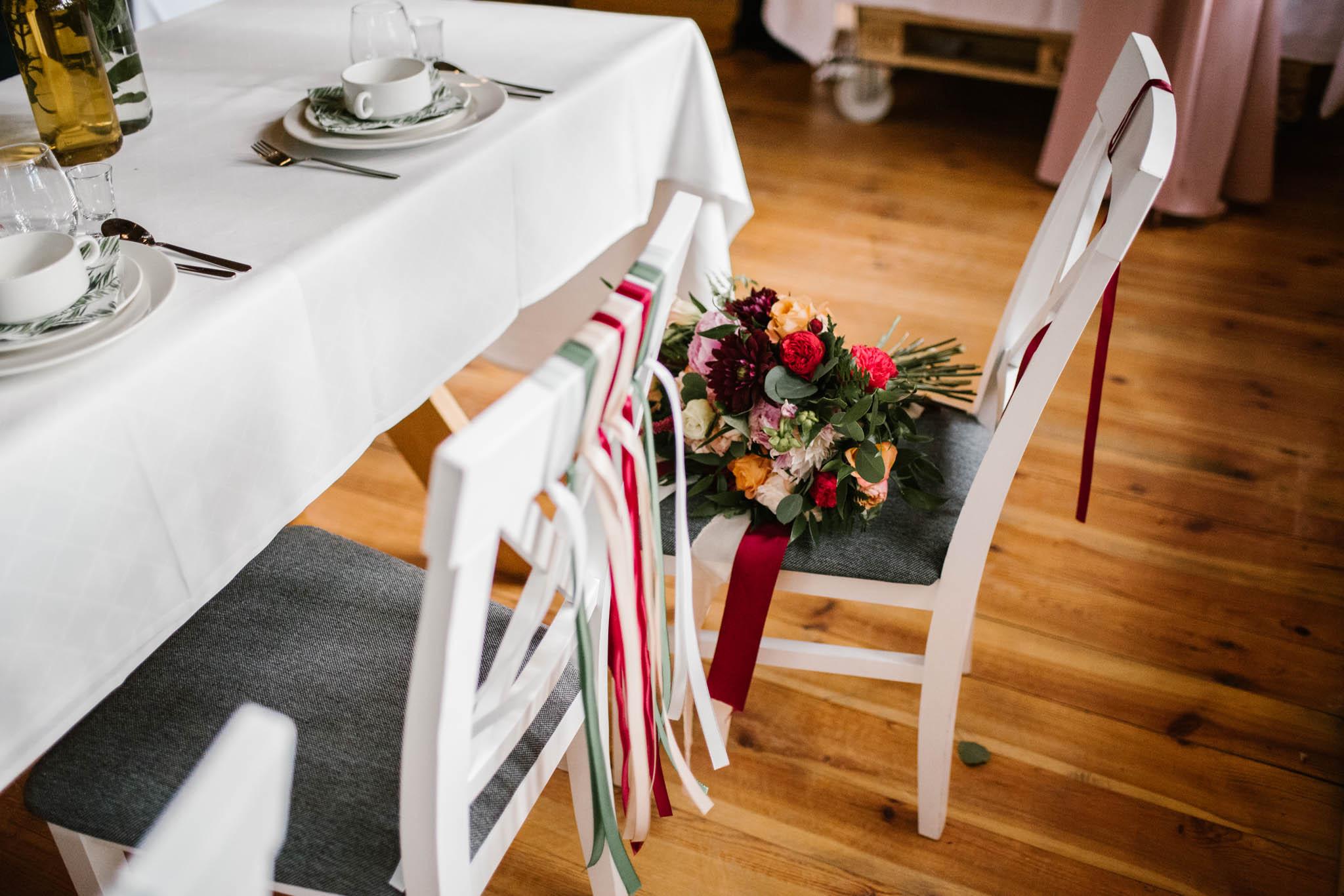 Dekoracje na krzesłach w sali weselnej - sesja ślubna na Wyspie Św. Edwarda Zaniemyśl