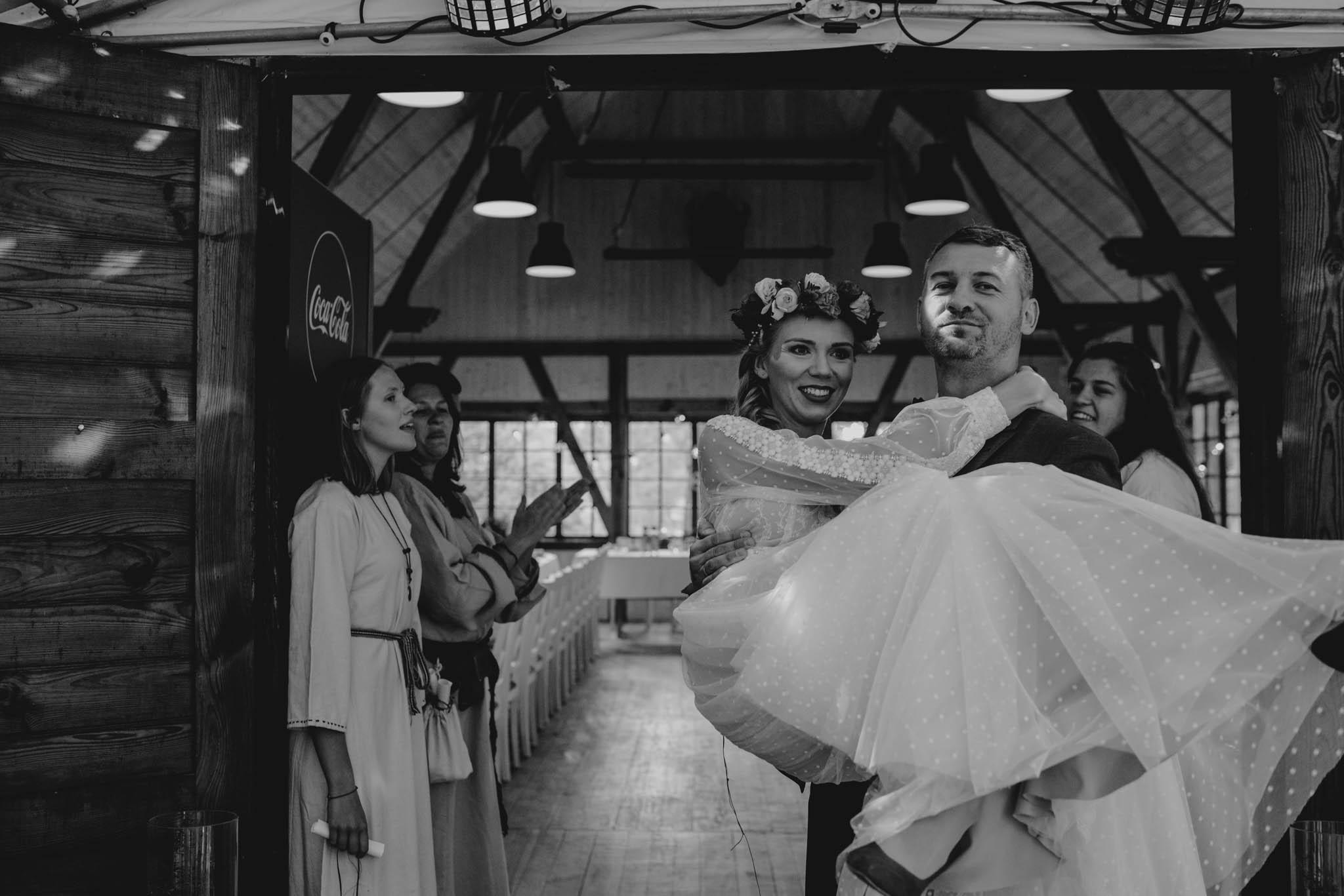 Mąż wnosi żonę na salę weselną - sesja ślubna na Wyspie Św. Edwarda Zaniemyśl