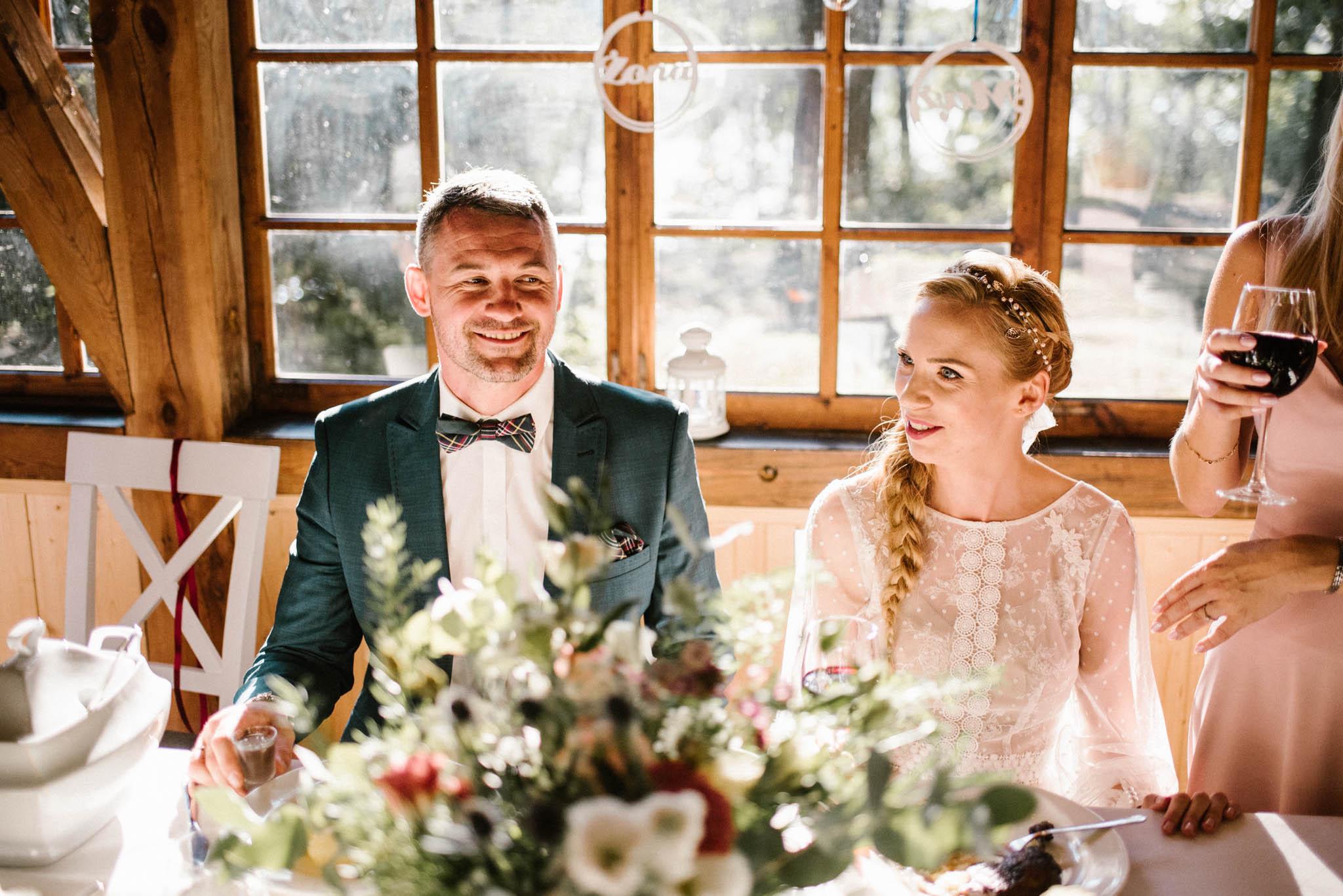 Małżeństwo siedzi przy stole pary młodej - sesja ślubna na Wyspie Św. Edwarda Zaniemyśl