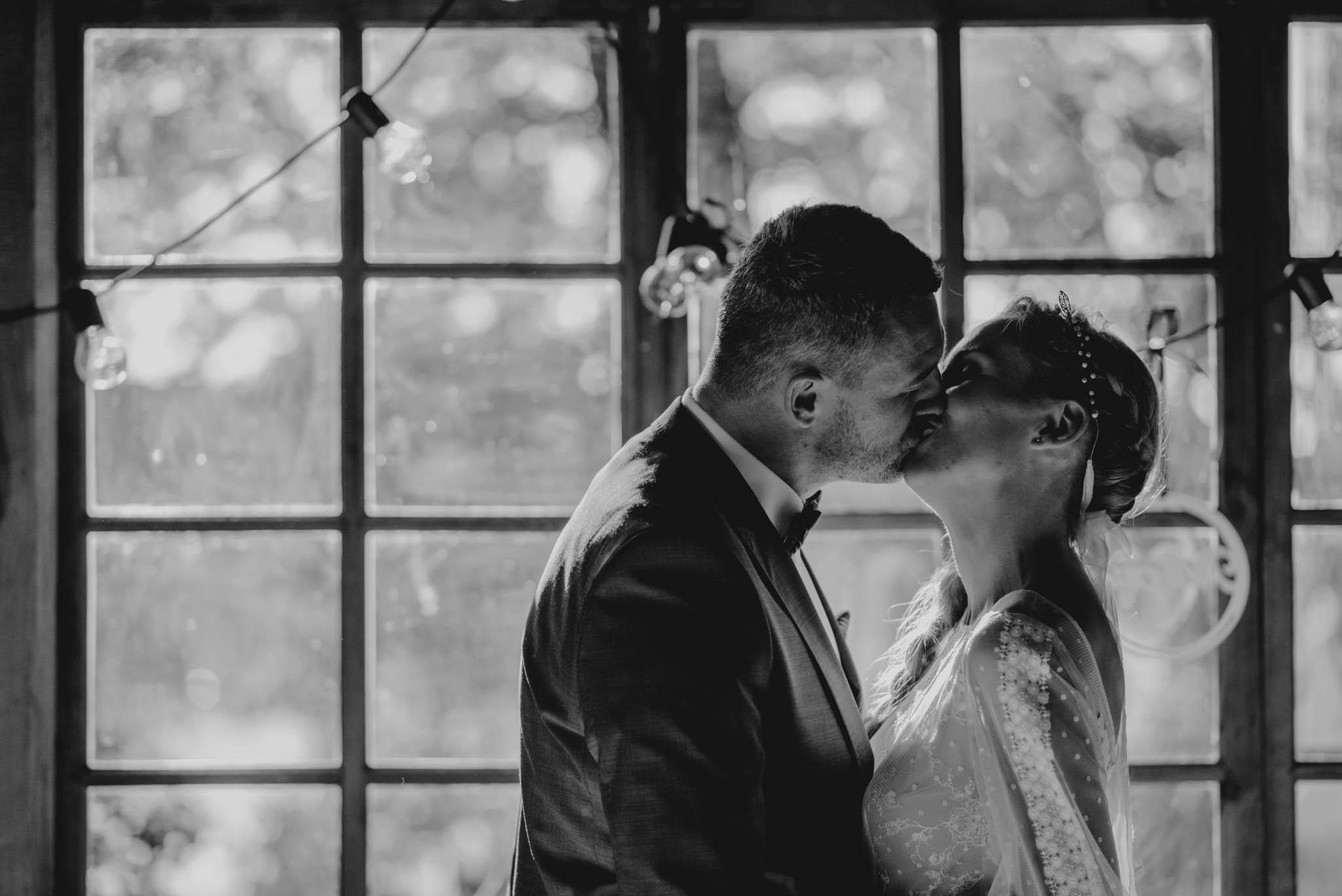 Para młoda całuje się przy stole - sesja ślubna na Wyspie Św. Edwarda Zaniemyśl