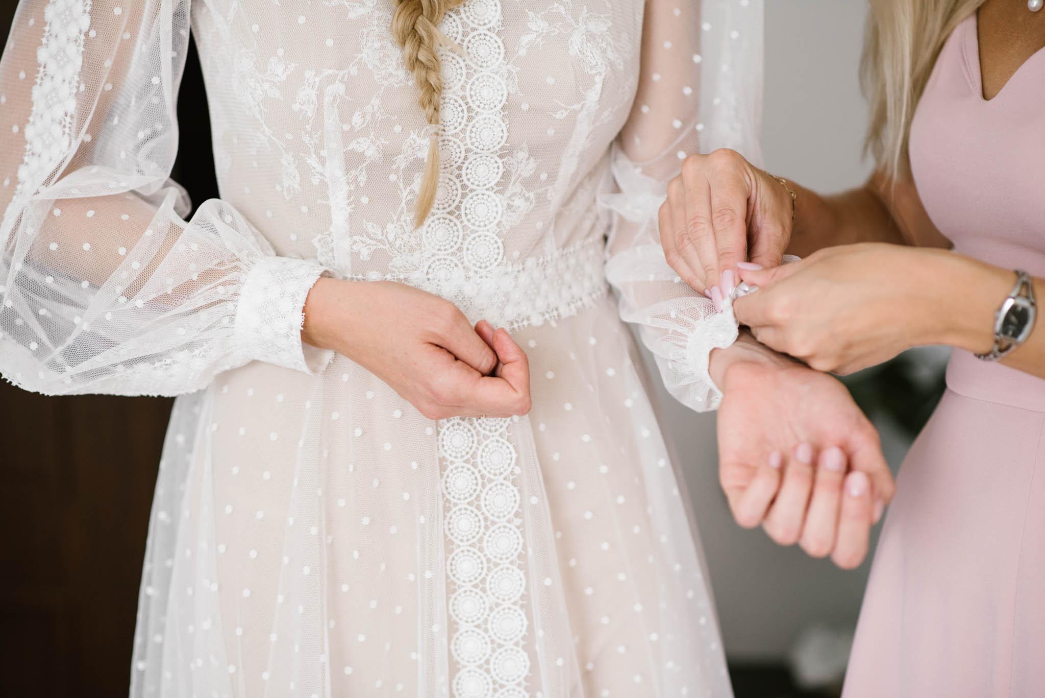 Druhna zapina pannie młodej guzik od sukni ślubnej - sesja ślubna na Wyspie Św. Edwarda Zaniemyśl