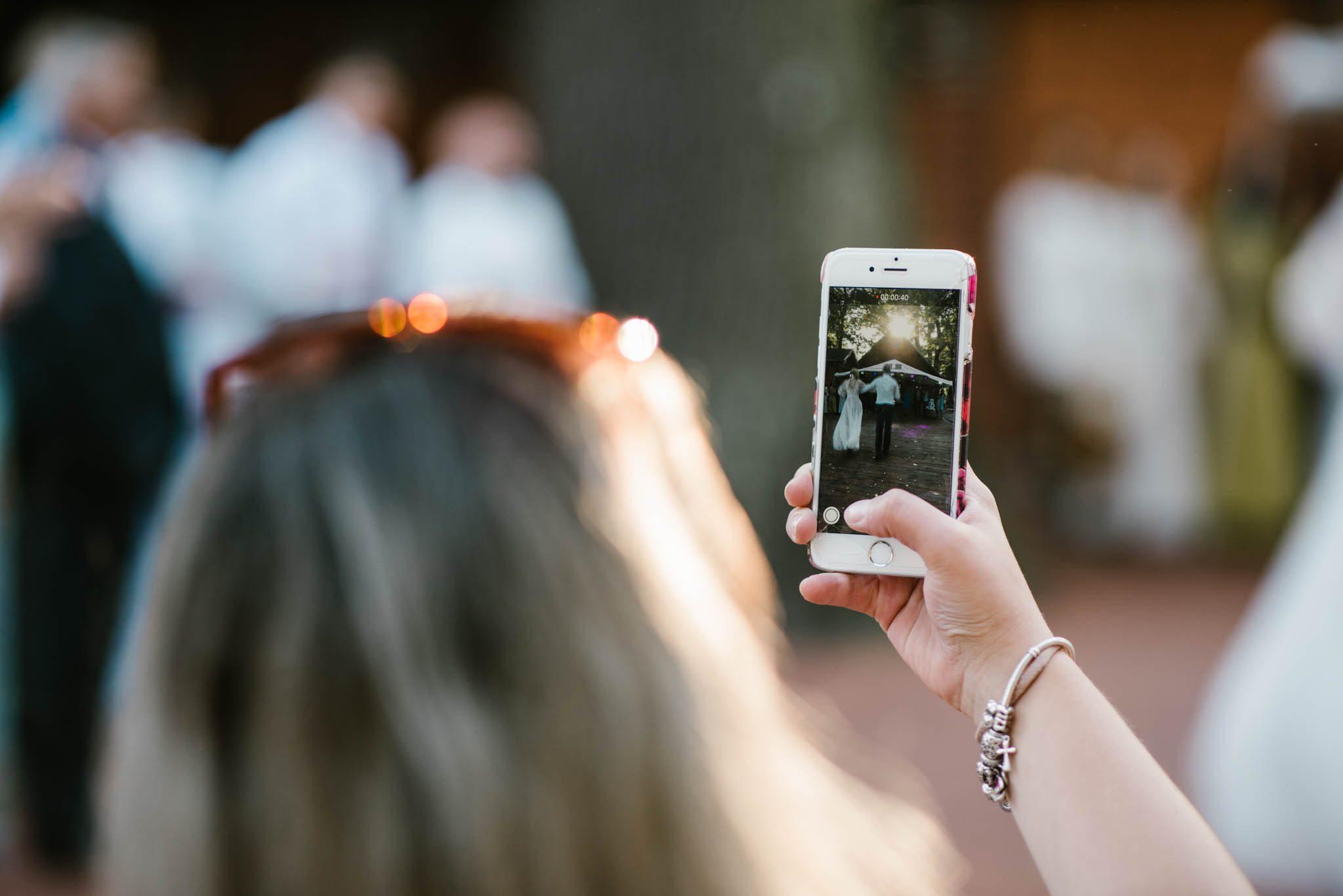 Pani fotografuje parę młodą telefonem - sesja ślubna na Wyspie Św. Edwarda Zaniemyśl