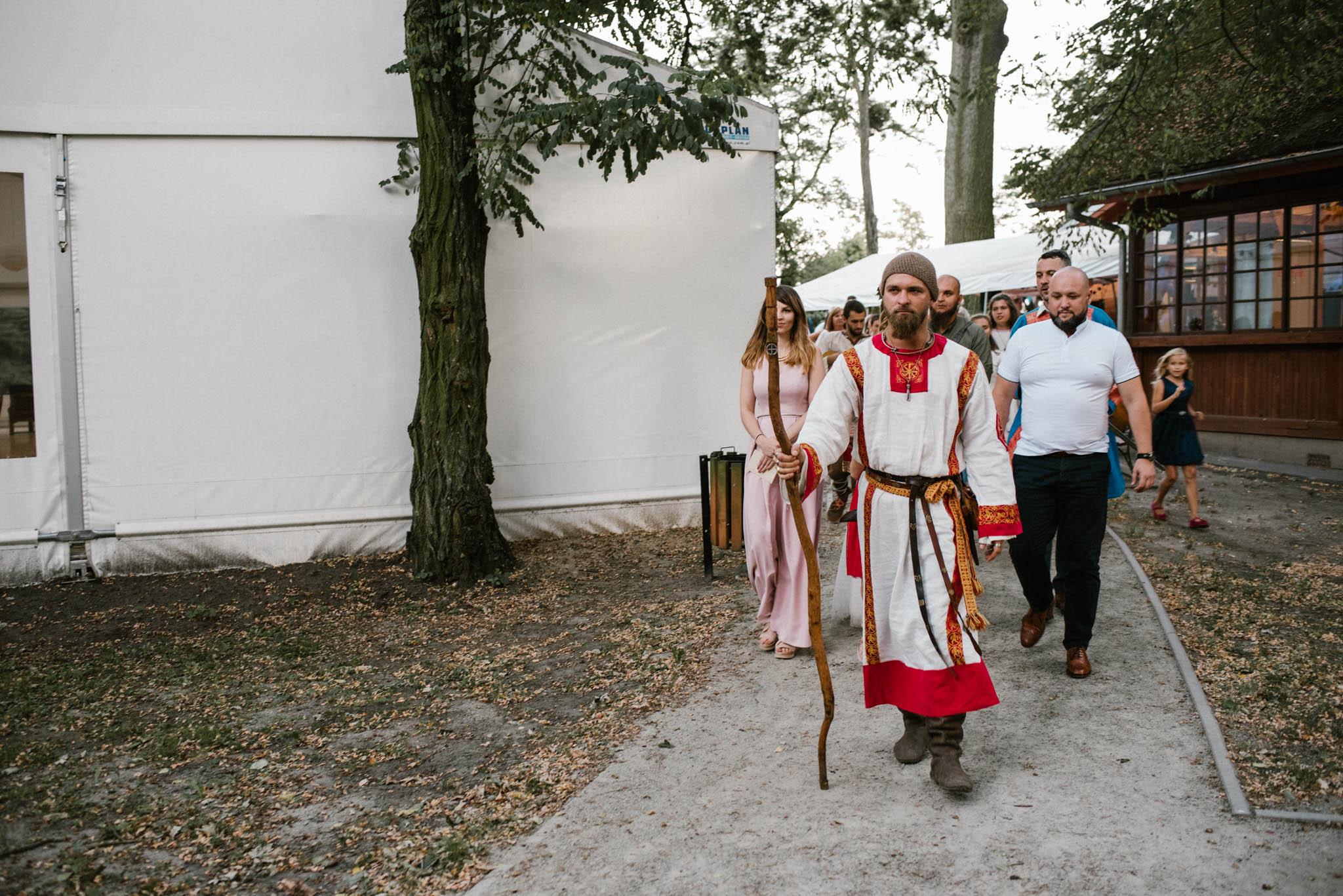 Goście weselni idą po chodniku - sesja ślubna na Wyspie Św. Edwarda Zaniemyśl