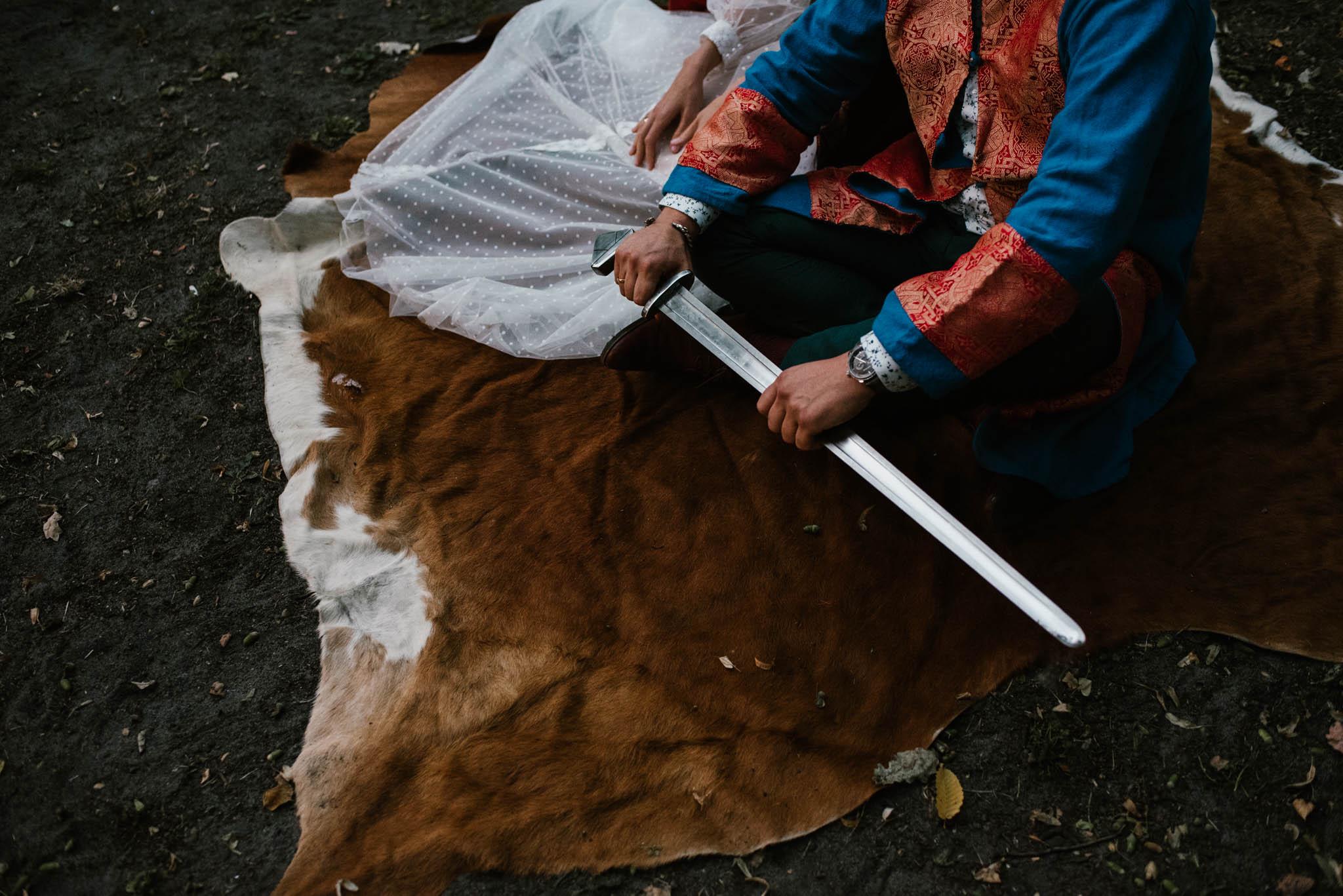 Pan młody trzyma miecz - sesja ślubna na Wyspie Św. Edwarda Zaniemyśl