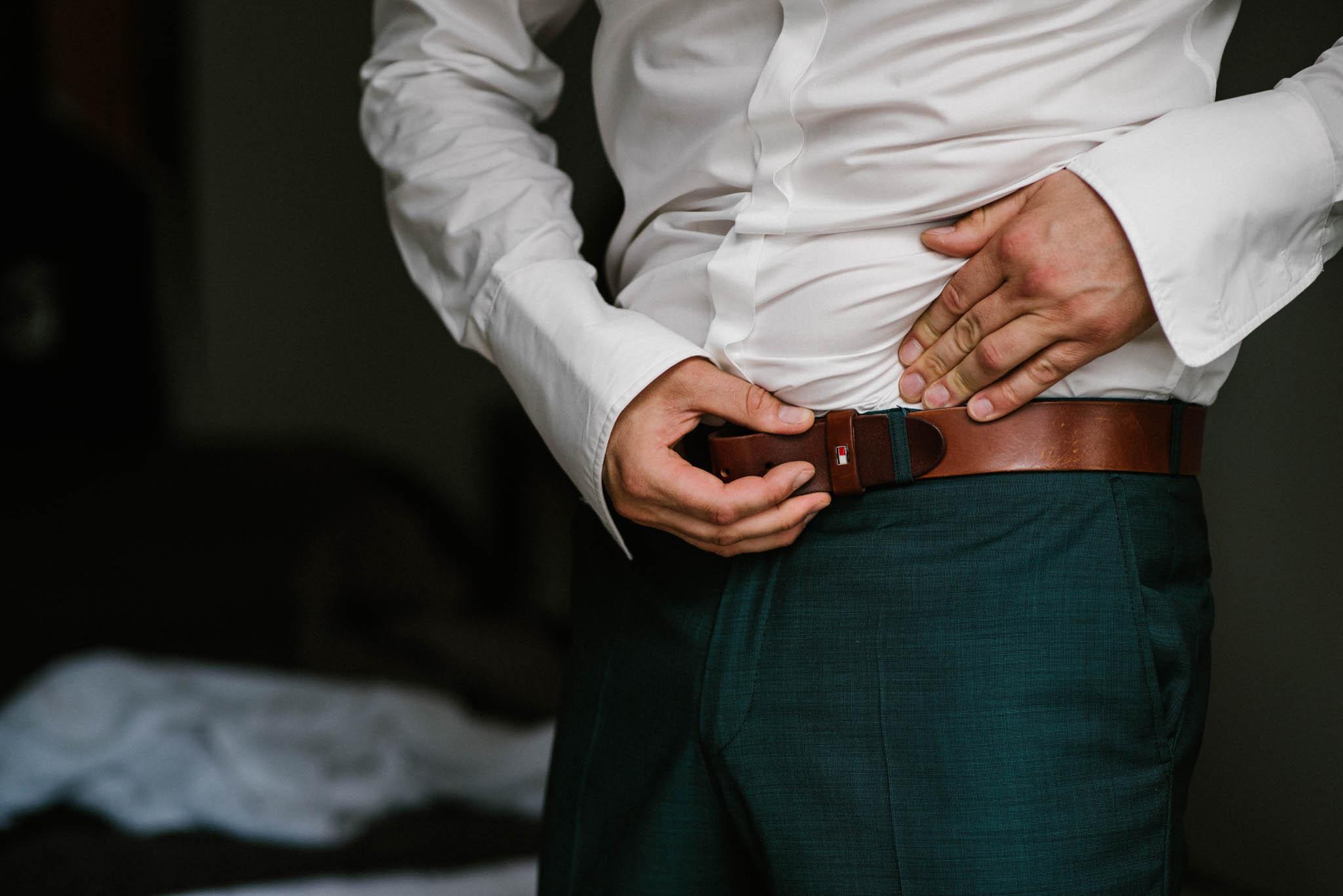Narzeczony zapina pasek od spodni - sesja ślubna na Wyspie Św. Edwarda Zaniemyśl