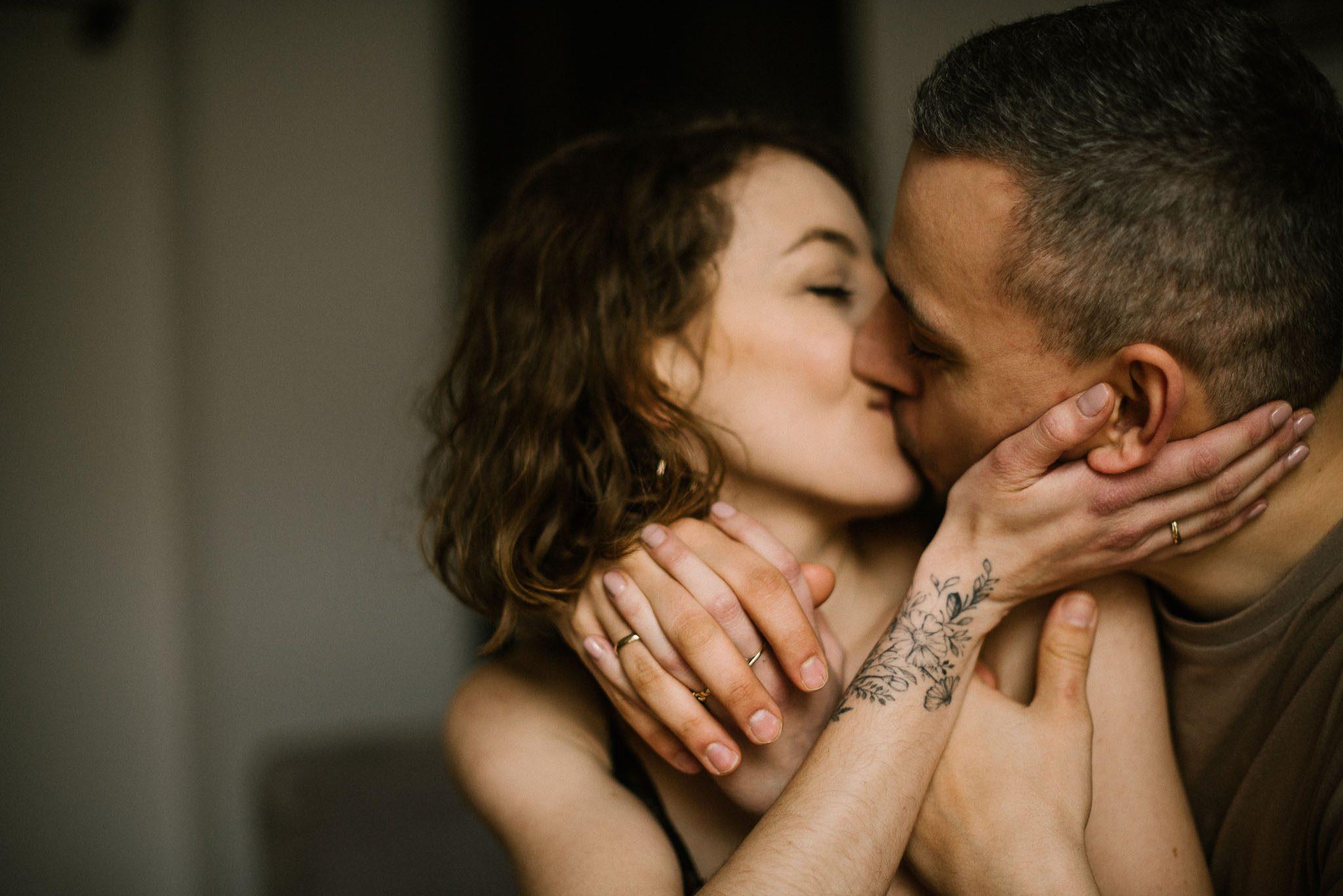 Żona całuje męża i głaszcze go po twarzy - sesja sensualna pary lifestyle w Poznaniu
