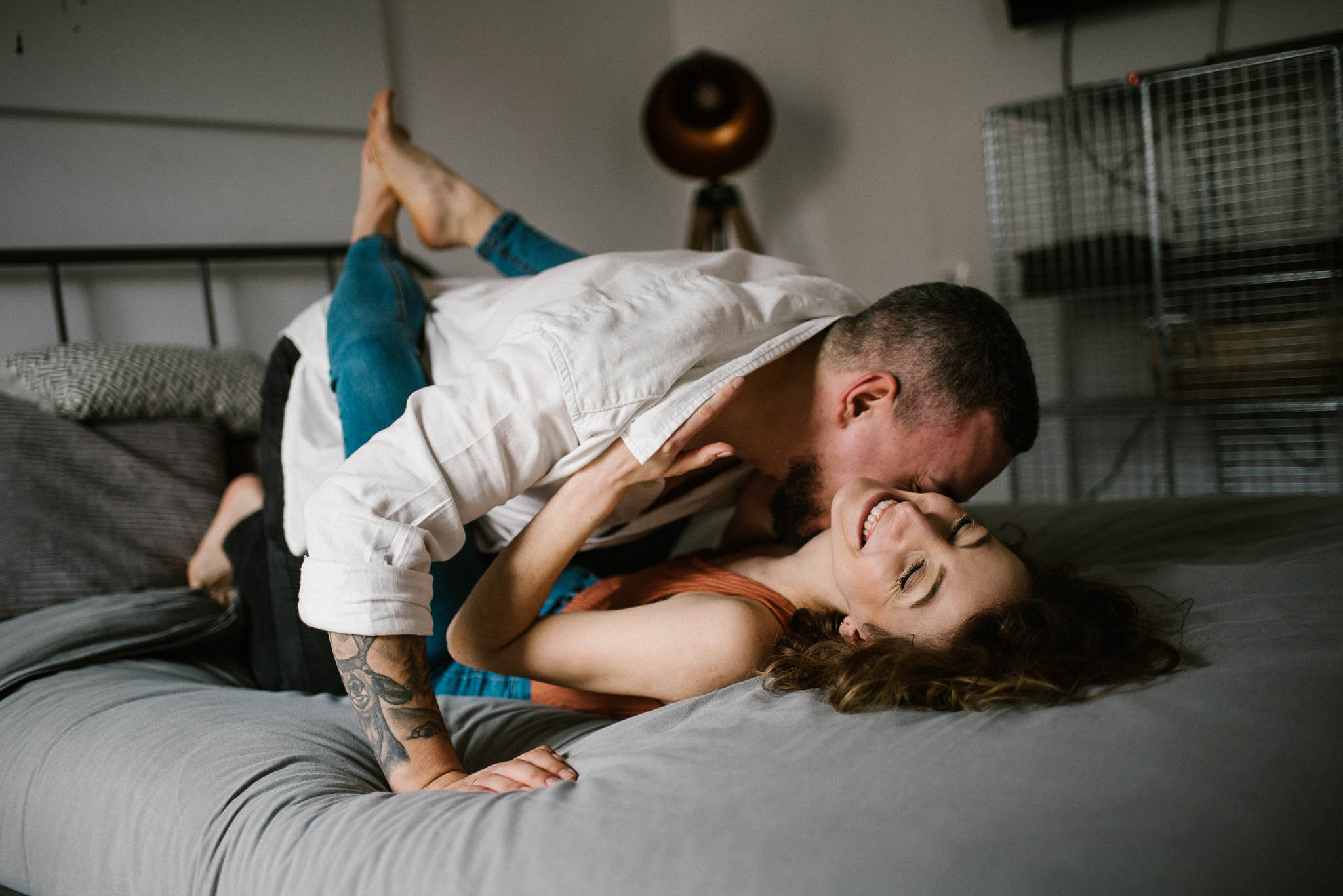 Narzeczony całuje partnerkę w szyję na łóżku w sypialni - sesja sensualna pary lifestyle w Poznaniu