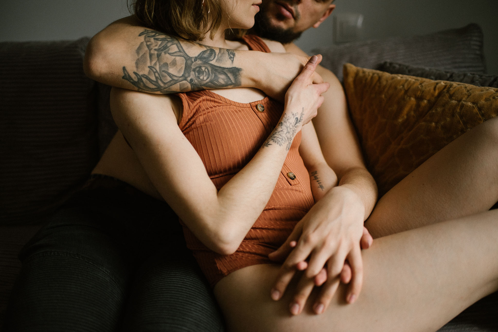 Partnerzy przytulają się na kanapie - sesja sensualna pary lifestyle w Poznaniu