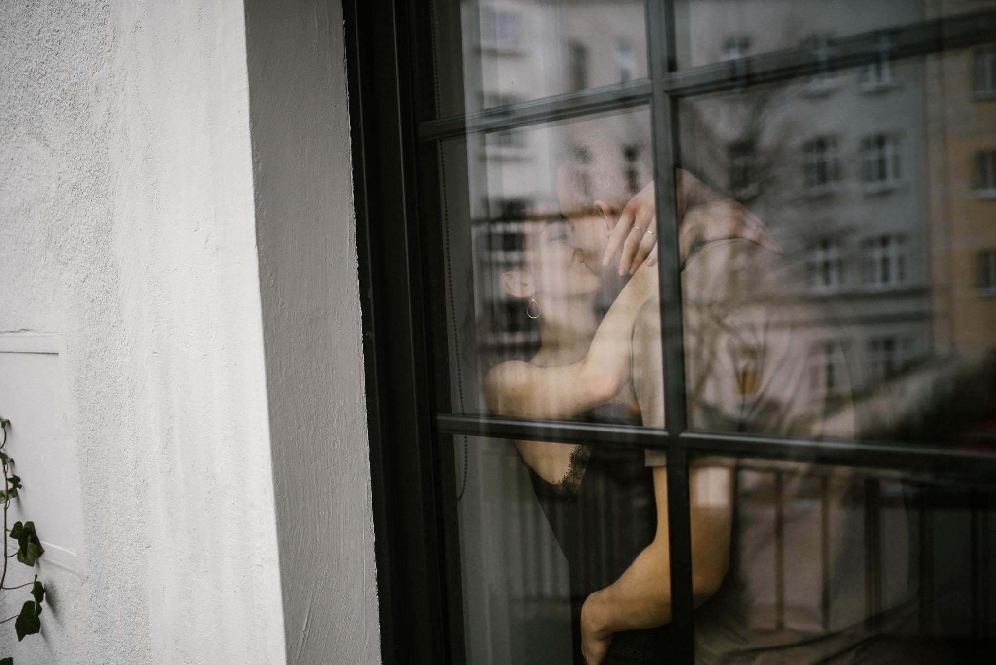 Chłopak całuje dziewczynę przy oknie - sesja sensualna pary lifestyle w Poznaniu