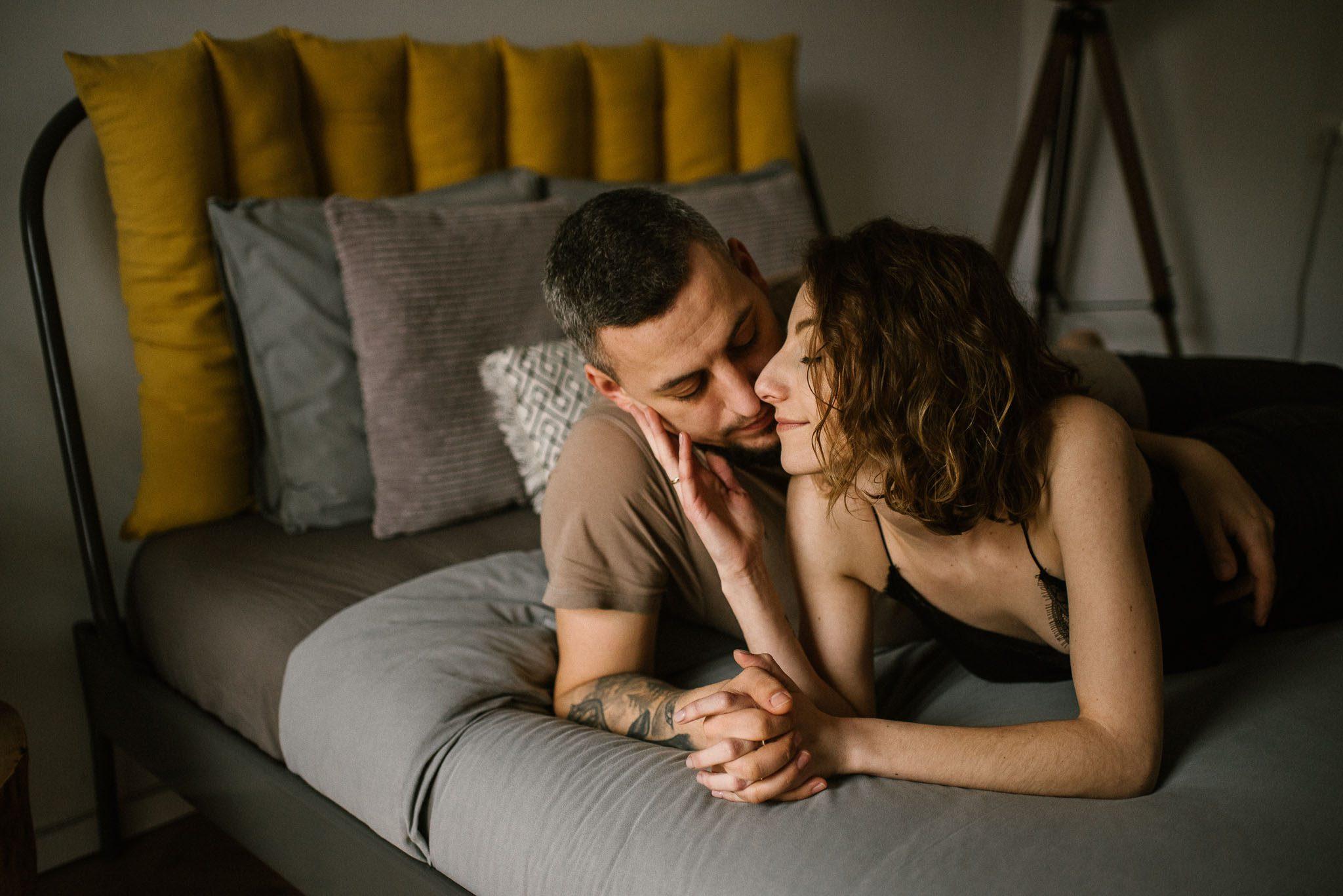 Małżeństwo leży na łóżku i patrzy na siebie - sesja sensualna pary lifestyle w Poznaniu