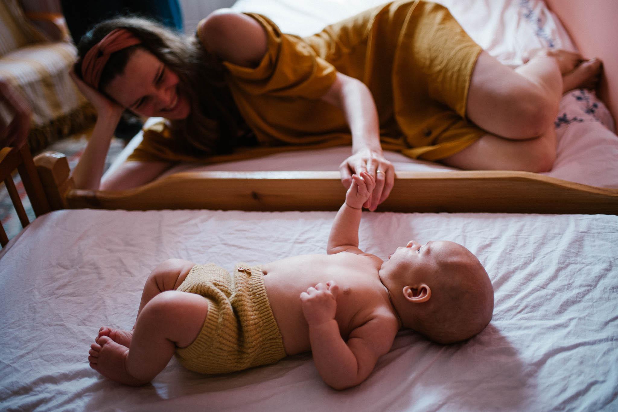 Mama trzyma niemowlę za rączkę, kiedy leży w łóżeczku - sesja niemowlęca lifestyle w domu Poznań