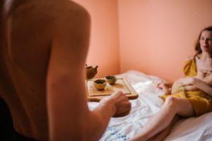 Mąż przyniósł żonie herbatę do łóżka - Sesja niemowlęca lifestyle w domu Poznań