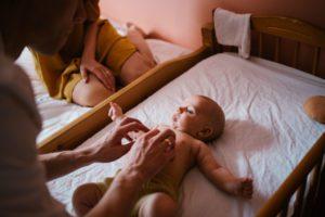 Rodzice budzą niemowlę w łóżeczku - sesja niemowlęca lifestyle w domu Poznań