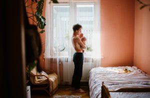 tata nosi synka na rękach -Sesja niemowlęca lifestyle w domu Poznań