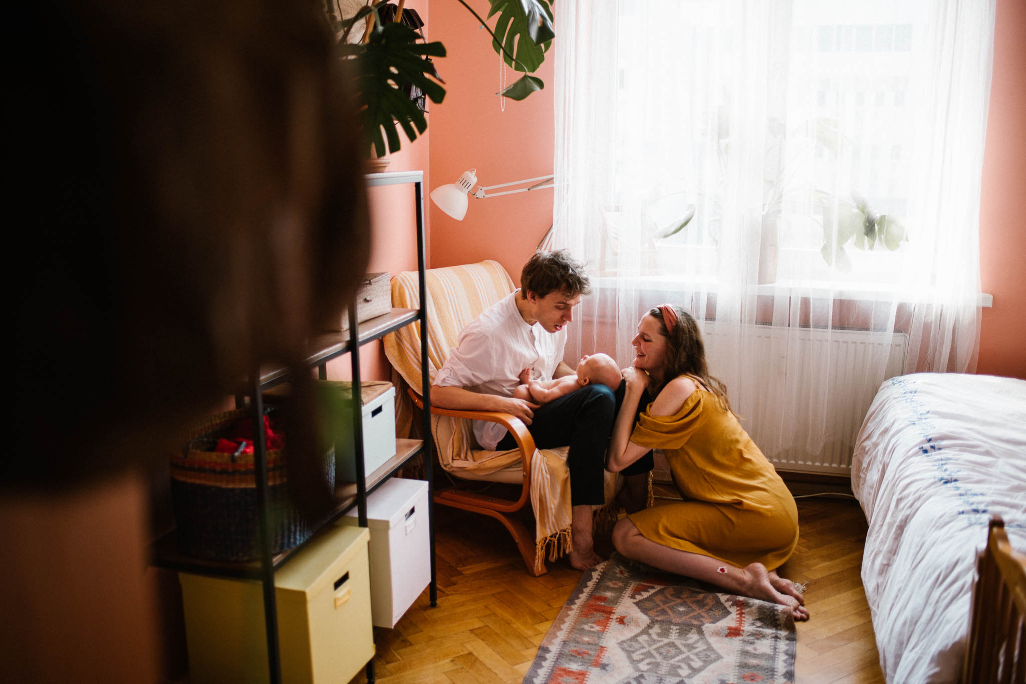 Tata trzyma niemowlę na kolanach, mama siedzi obok nich -Sesja niemowlęca lifestyle w domu Poznań