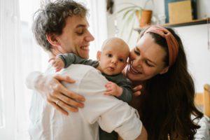 Rodzice przytulają niemowlę -Sesja niemowlęca lifestyle w domu Poznań