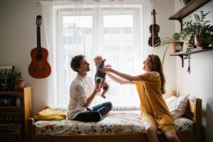 tata przekazuje niemowlę mamie na łóżku - Sesja niemowlęca lifestyle w domu Poznań