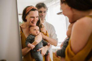 Rodzina przegląda się z niemowlęciem w lustrze - Sesja niemowlęca lifestyle w domu Poznań