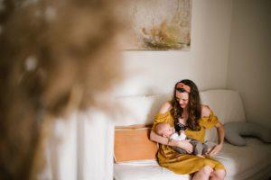 Mama siedzi z niemowlęciem na sofie - Sesja niemowlęca lifestyle w domu Poznań