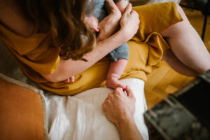tata dotyka stópek niemowlęcia - Sesja niemowlęca lifestyle w domu Poznań