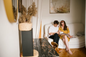 Rodzice z niemowlęciem siedzą na sofie - Sesja niemowlęca lifestyle w domu Poznań