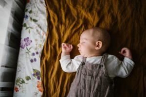 Niemowlę śpi w łóżeczku -Sesja niemowlęca lifestyle w domu Poznań