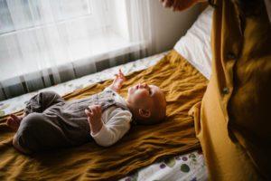 Niemowlę obudziło się w łóżeczku - Sesja niemowlęca lifestyle w domu Poznań