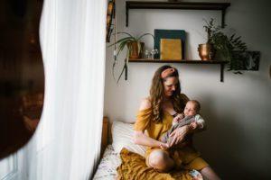 Mama trzyma synka na rękach - Sesja niemowlęca lifestyle w domu Poznań