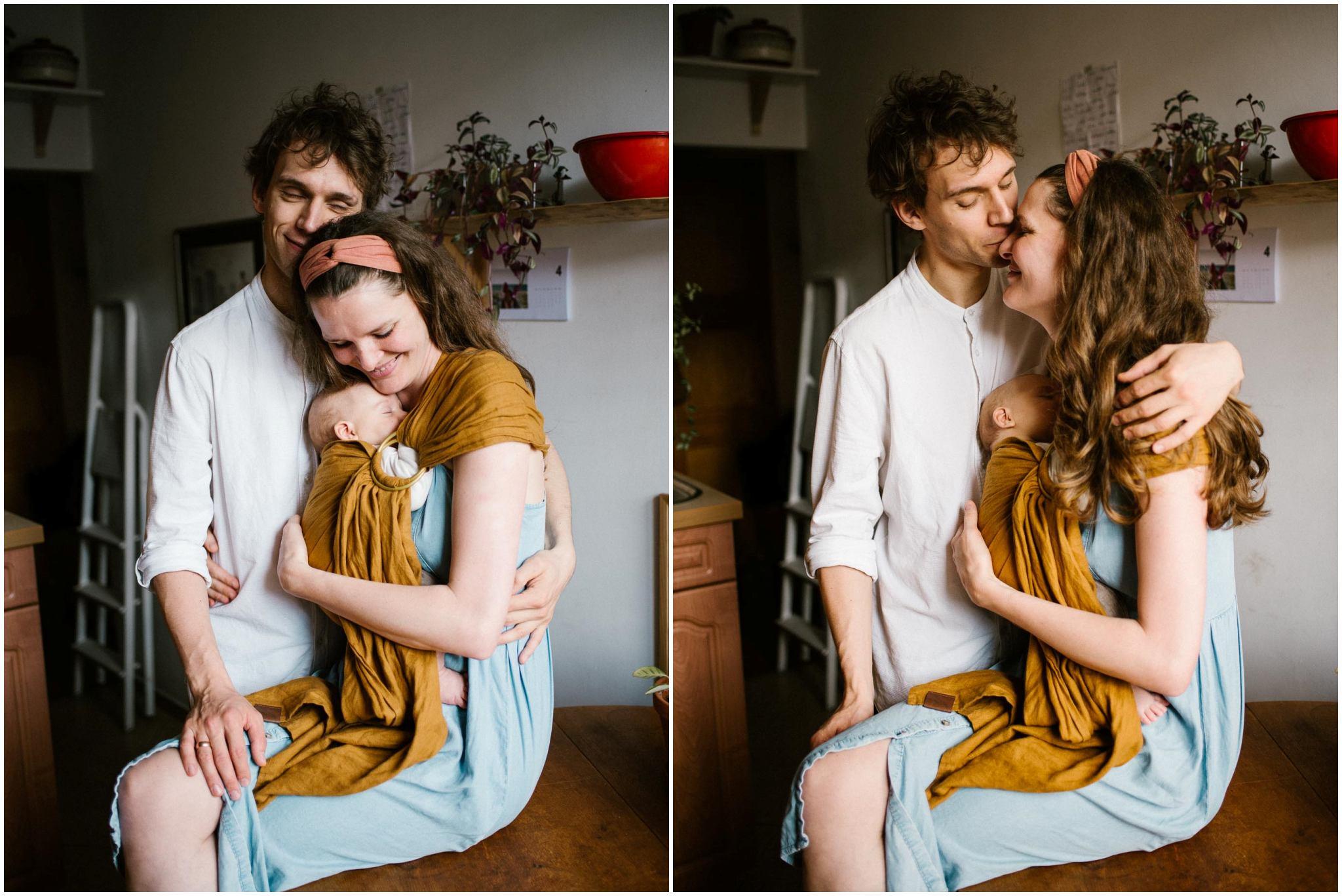 Mama z niemowlęciem zawiązanym w chustę, przytula ich tata - Sesja niemowlęca lifestyle w domu Poznań