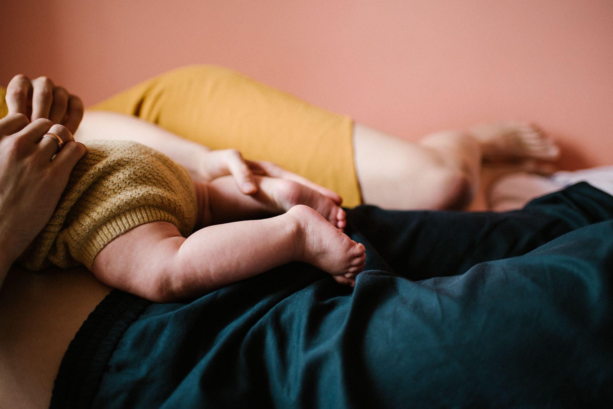 Stópki niemowlęcia leżącego na tacie - sesja niemowlęca lifestyle w domu Poznań