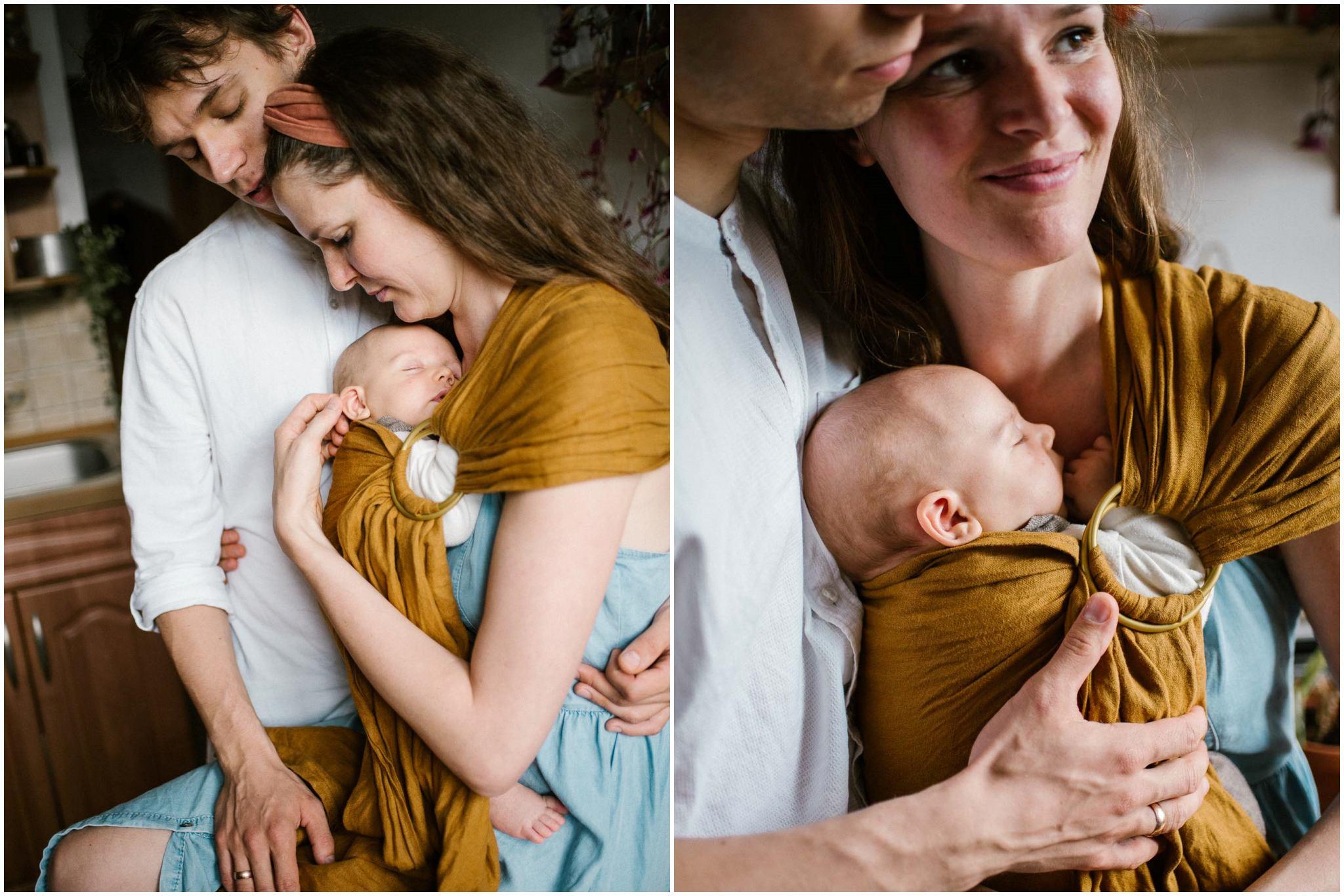 Mama i tata przytulają niemowlę, które jest zawinięte w chustę - Sesja niemowlęca lifestyle w domu Poznań