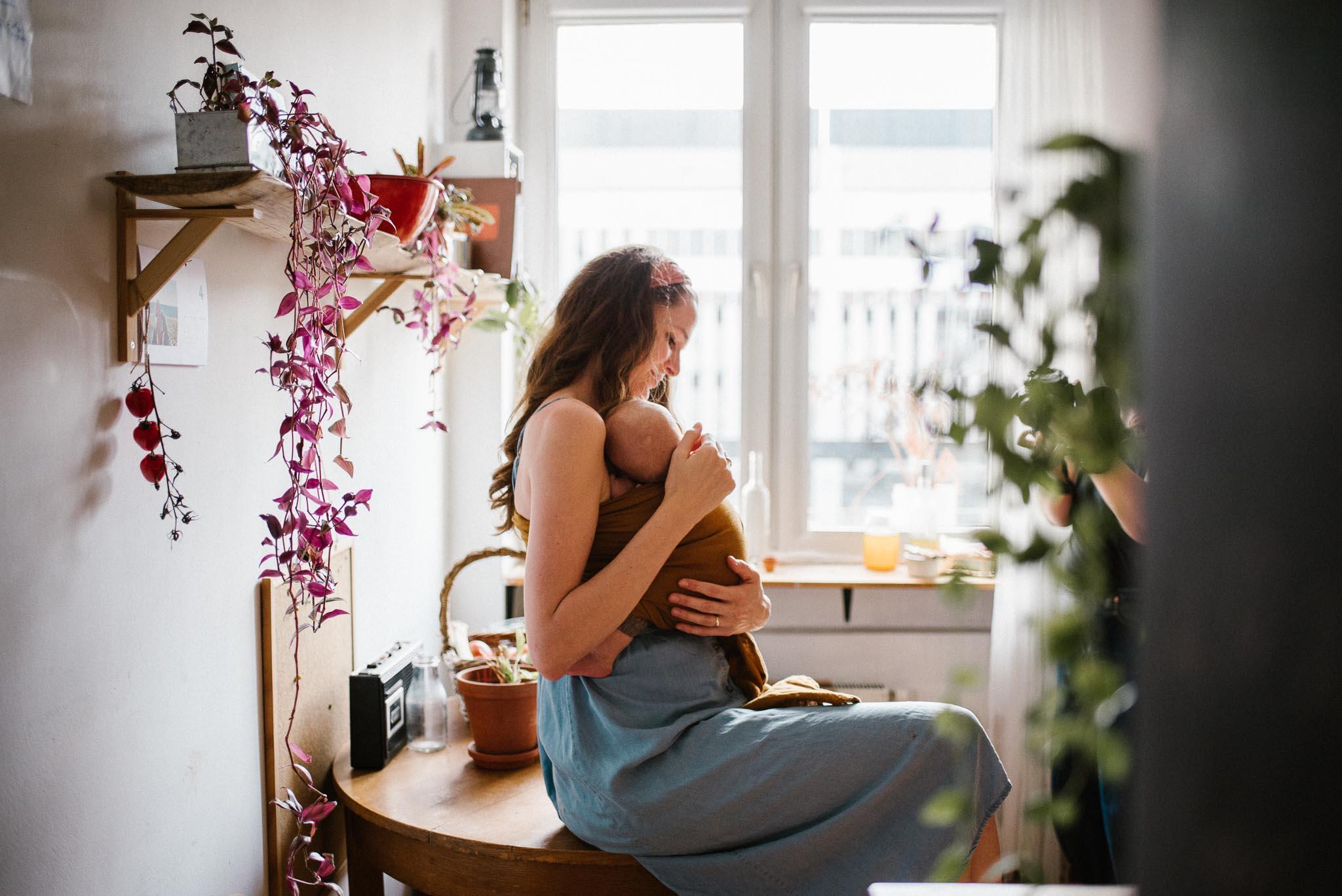 Mama nosi niemowlę w chuście - Sesja niemowlęca lifestyle w domu Poznań