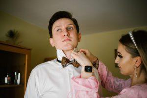 Świadkowa przypina muchę panu młodemu - sesja ślubna reportaż Żuczki Inowrocław
