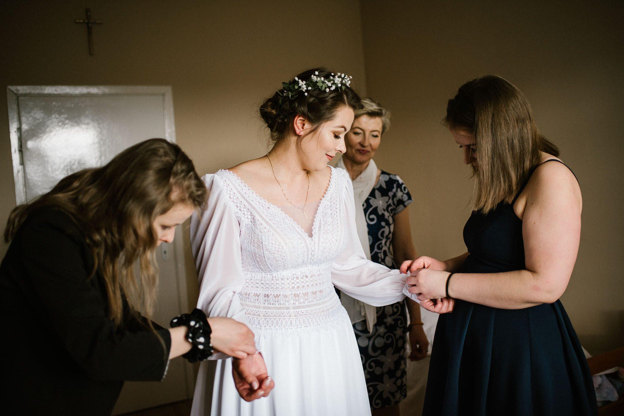 Przyjaciółki pomagają pannie młodej zapiąć suknię ślubną - sesja ślubna reportaż Żuczki Inowrocław